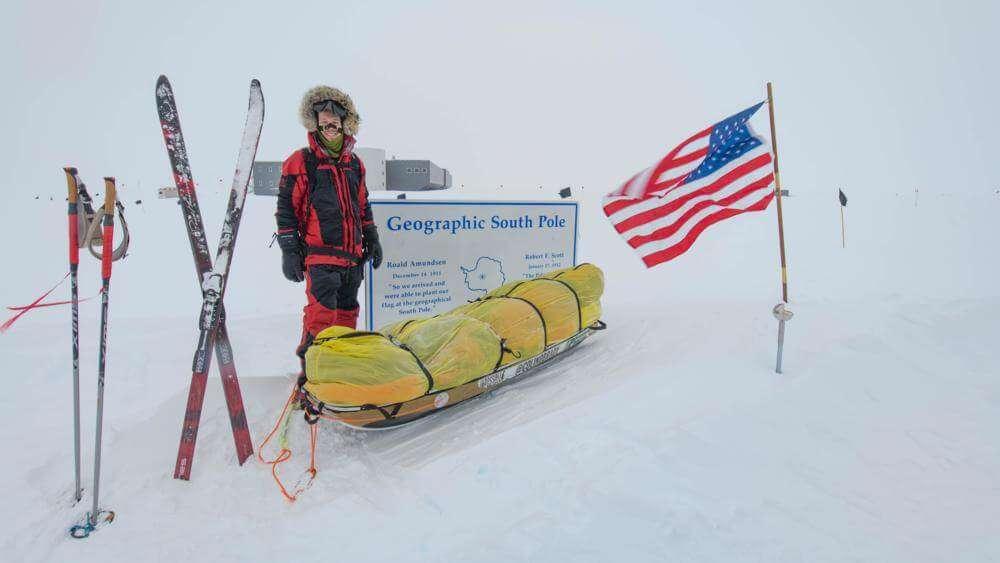 """Колін О'Брейді стоїться коло таблички з написом """"Географічний південний полюс"""". Ліворуч сани, а праворуч прапор США."""