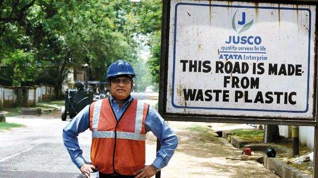 Працівник поряд зі знаком «Цю дорогу зроблено з пластику». Індія.