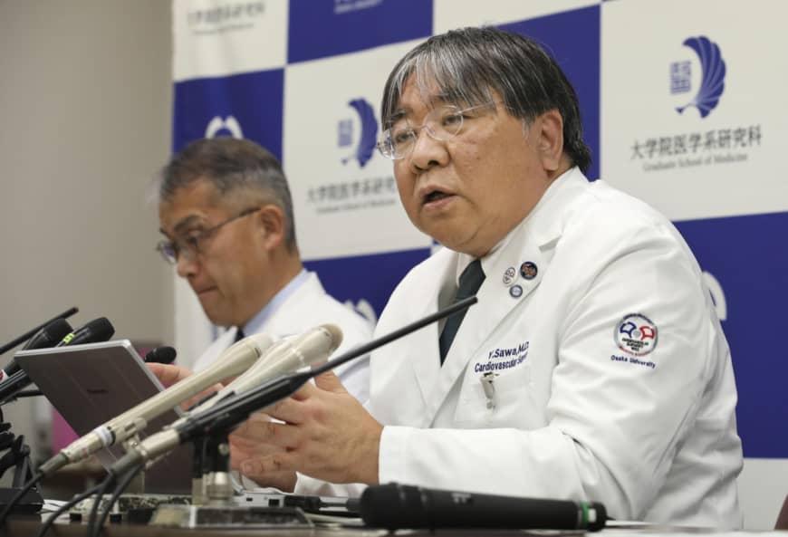 Пресконференція, де професор відділення серцево-судинної хірургії Осакського Університету Йошікі Сава розповідає про трансплантацію серцевих клітин.Чоловік у халаті (медик) японець сидить за столом перед мікрофоном, а на тлі ще хтось у халаті, але не японець.